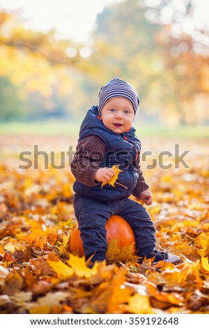 beautiful young boy sitting on a pumpkin - stock photo