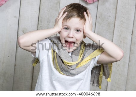 Beautiful young boy smiling and holding his head. Joyful surprise. - stock photo