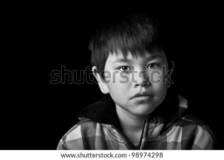 Beautiful young boy with bright eyes and concerned look on black background in black and white