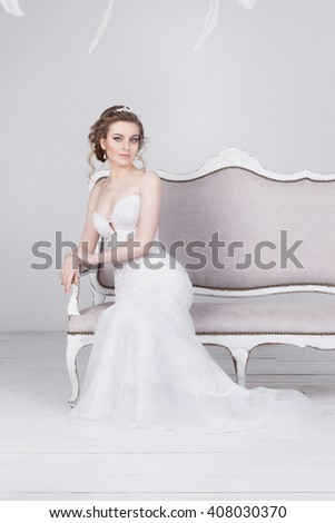Beautiful young bride in a luxurious lace wedding dress. She sits on a white vintage sofa. She is an elegant and slim, she has pale skin, dark blond hair and blue eyes. The dress has a lace train. - stock photo