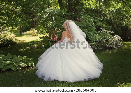 Beautiful young bride in a magnificent wedding dress spinning in nature, happiness, fun