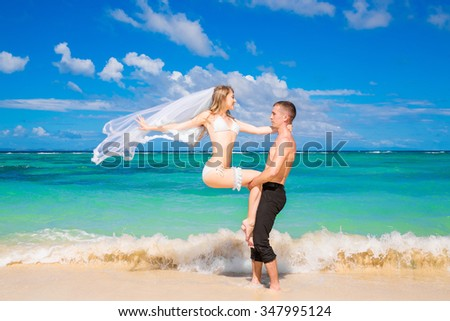 Beautiful young bride in a white bikini, veil and garter on her leg and groom on the tropical beach.  Wedding and honeymoon on the tropical island.