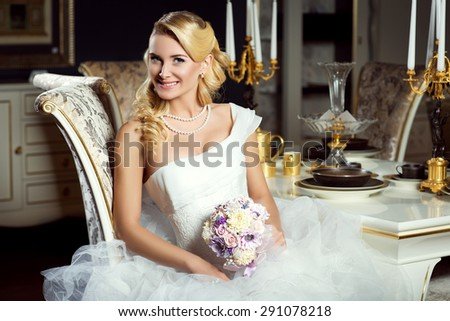 Beautiful young bride in fashionable gown with floral bouquet sitting near dinner table. Interior photo. - stock photo