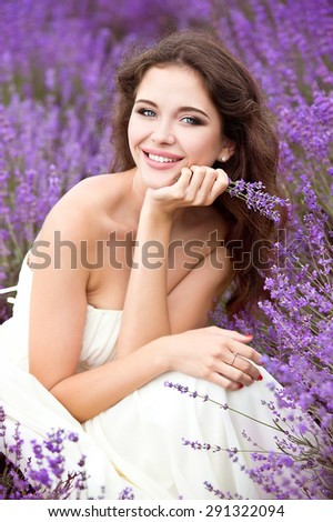 Beautiful young bride in lavender field, happy woman enjoying lavender flowers. - stock photo
