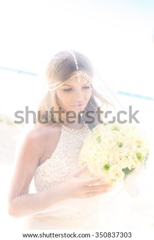Beautiful young bride in the veil, with wedding bouquet of white roses on the tropical beach. Summer vacation concept.