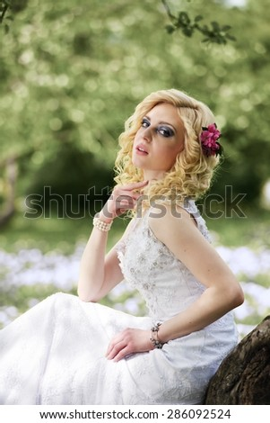 Beautiful young bride in white dress sits on tree in summer green park