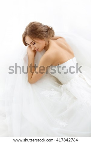 Beautiful young bride in white wedding dress indoors.  Luxuty model lying and sleeping over white backgroung. Girl waiting her groom in bright room. Beautiful wedding hairdress. High key photo. - stock photo
