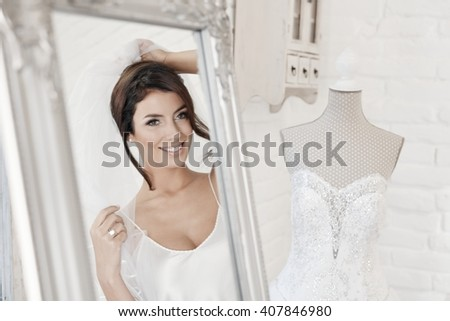 Beautiful young bride looking at herself in mirror while trying on veil on wedding-day. - stock photo