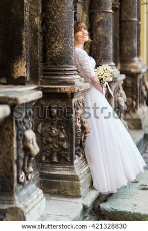 Beautiful young bride looking towards between the columns of old building and holding bridal bouquet