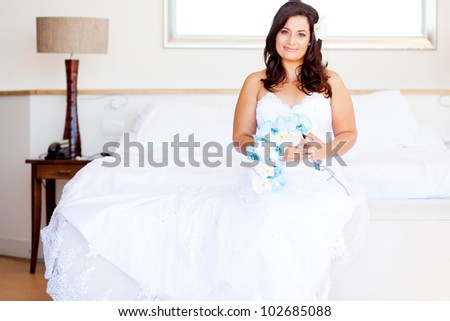 beautiful young bride sitting on bed with bouquet - stock photo