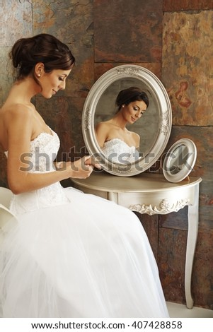 Beautiful young bride sitting on chair front of mirror. Side view. - stock photo