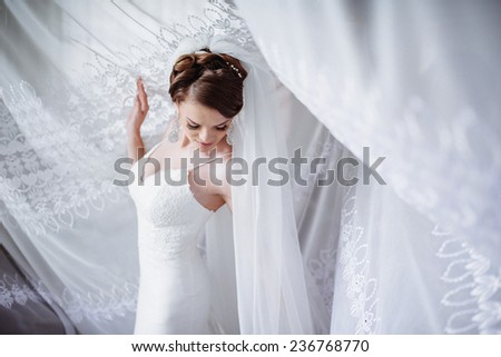 beautiful young bride standing beside a large window waiting  - stock photo