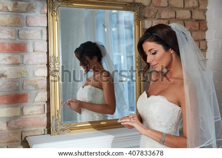 Beautiful young bride standing front of mirror, looking at engagement ring. Side view. - stock photo