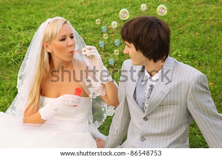 Beautiful young bride wearing white dress sitting on green grass with groom and blowing bubbles; focus on man