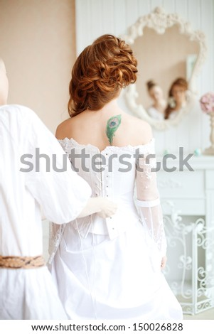 Beautiful young bride wears dress by stylist - stock photo