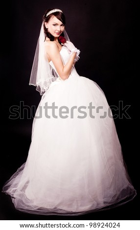 beautiful young bride with a rose, isolated against black studio background - stock photo
