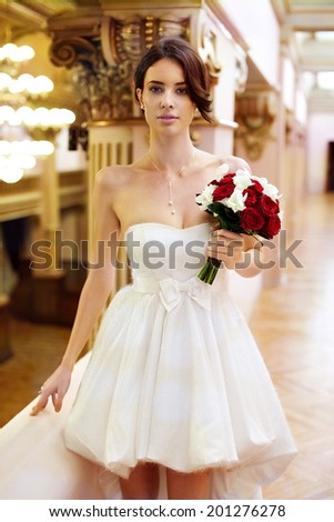 Beautiful young bride with a short gown and a bouquet in ger hand looking straight - stock photo
