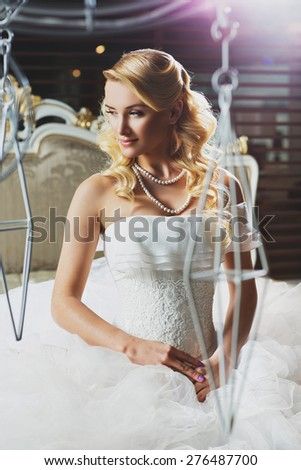 Beautiful young bride with long curly hair in fancy dress sitting on bed - stock photo