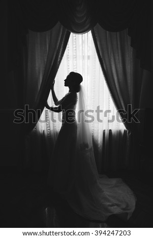 Beautiful young bride with wedding makeup and hairstyle in bedroom. Happy Bride waiting groom. Marriage Wedding day moment. Bride portrait