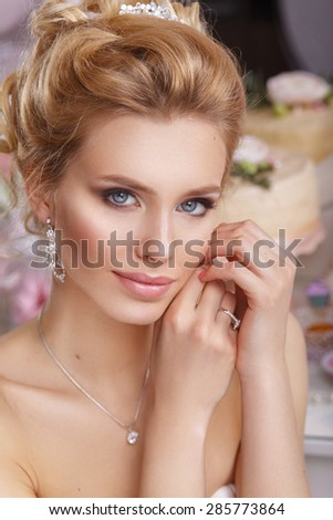 Beautiful young bride with wedding makeup and hairstyle in bedroom, newlywed woman final preparation for wedding. Happy Bride waiting groom. Marriage Wedding day moment.  - stock photo