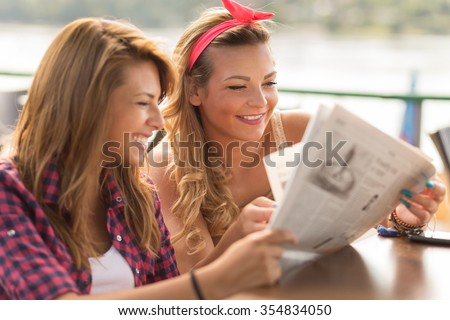 Beautiful young brunette and blond girl sitting in a cafe, drinking coffee and reading newspapers - stock photo