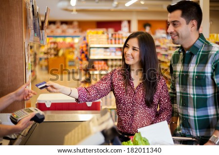 Beautiful young brunette and her boyfriend buying some groceries at the supermarket and paying with a credit card - stock photo