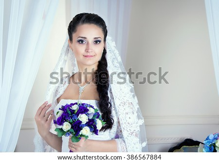 beautiful young brunette bride in a white wedding dress, and long lacy veil standing in a room with white curtains, holding bouquet