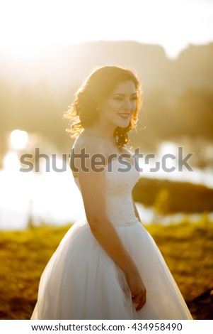 Beautiful young brunette bride in park - stock photo