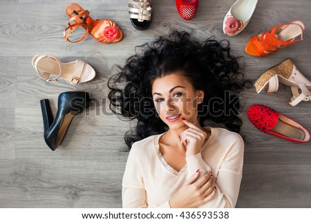 Beautiful young brunette cute funny girl lying on the floor around her laid out different shoes, sandals, ballet flats, a girl can not choose what kind of shoes to wear, fashion, emotion, top view - stock photo