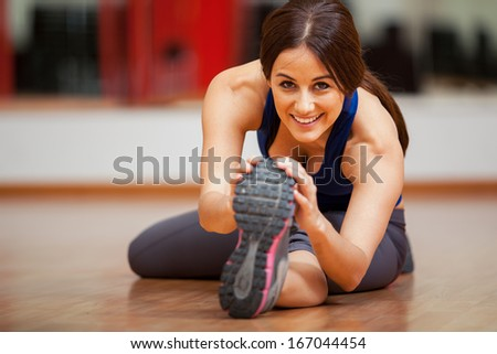 Beautiful young brunette doing some stretching exercises and smiling - stock photo