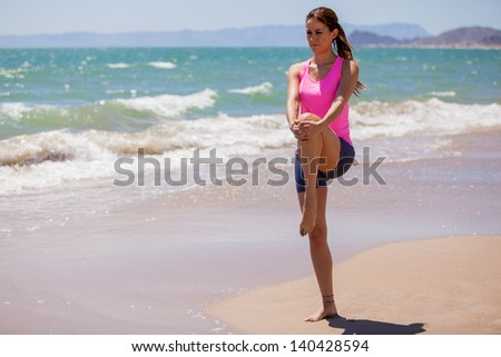 Beautiful young brunette doing some stretching exercises before running at the beach