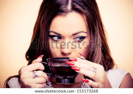 Beautiful young brunette drinking coffee, on the beige background - stock photo