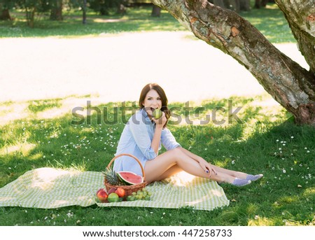 Beautiful, young brunette eating an apple in the park.