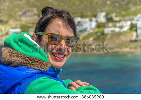 Beautiful young brunette enjoying the sun in Mykonos, Greece. - stock photo