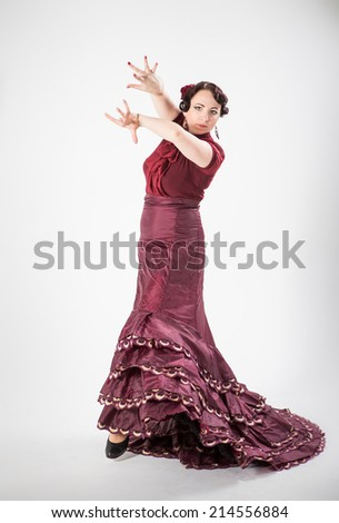 beautiful young brunette female spanish flamenco dancer in red blouse and vinous flamenco skirt dancing with her arms and skirt in studio on gray background - stock photo