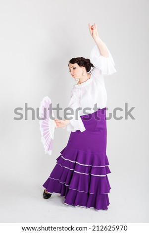 beautiful young brunette female spanish flamenco dancer in white shirt and purple flamenco skirt dancing with white and purple fan in her arms in studio on gray background - stock photo
