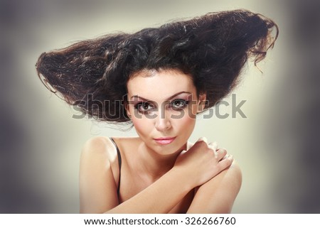 Beautiful young brunette female with bright fashion multicolored make-up. Studio photo. Fashion toning