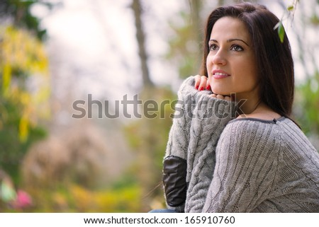 Beautiful young brunette girl at autumn park - stock photo