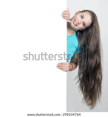 Beautiful young brunette girl holding blank white sign with copy space.  - stock photo