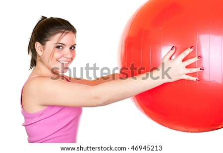 beautiful young brunette girl in pink exercising with big red ball