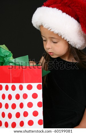 Beautiful young brunette girl looking into a gift bag - stock photo