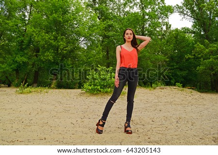 Beautiful young brunette girl posing in red blouse on background of the forest