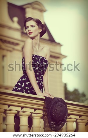 beautiful young brunette girl posing like vintage diva on balcony of ancient palace with elegant hair-style, red lipstick, short dress and hat in the hand .vintage color effect