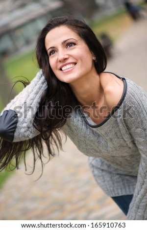 Beautiful young brunette girl smiling at park
