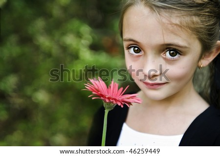 Beautiful young brunette girl with a great expression on her face holding a pink flower. - stock photo