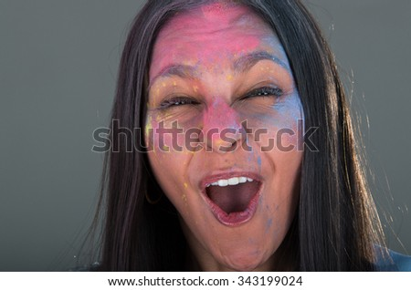 Beautiful young brunette girl with colorful decorated face celebrating
