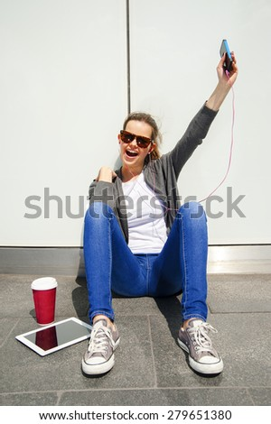 beautiful young brunette hair hipster woman listening music earphones in the city - stock photo