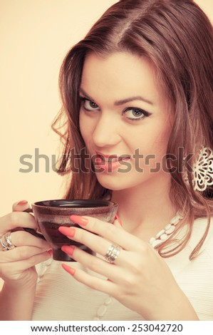 Beautiful young brunette holding cup of coffee, on beige background - stock photo