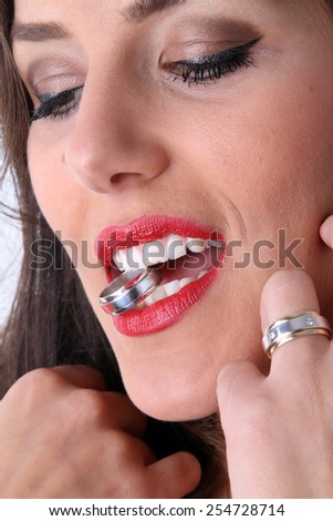 beautiful young brunette in a green blue corset with very red lipstick smiles and provocative posing for the camera with a gold wedding ring between the beautiful white teeth and a bright red lips - stock photo