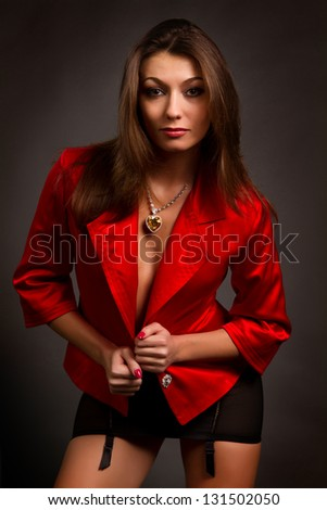 beautiful young brunette in a red jacket on a gray background